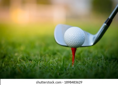 High-quality golf club hitting a white golf ball placed on a red peg with green grass.