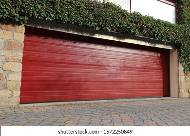 High-quality red garage door (sectional door) next to a residential building