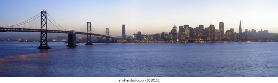 High-resolution panoramic image of Bay Bridge and San Francisco downtown decorated by Christmas lighting at dusk (shot from Treasure Island). Copyspace on
