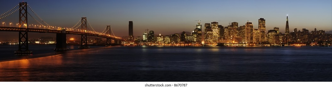 A high-resolution stitched image of Bay Bridge and San Francisco downtown decorated by Christmas lighting at dusk (shot from Treasure Island). Copyspace on top and bottom.