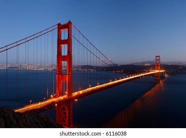 High-resolution stitched image of Golden Gate Bridge glowing in the dusk.