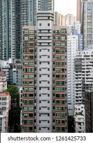 High-rise apartment building stands among other tall buildings in city environment