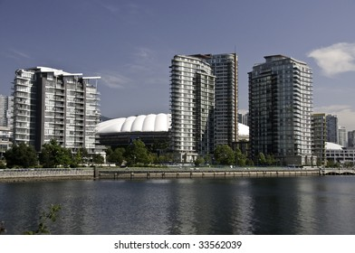 Highrise buildings by the sea side in Vancouver.The white dome is the stadium which will hold the openning ceremonies for the 2010 winter Olympics.Vancouver British Columbia