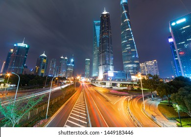 High-rise buildings, overpasses, and heavy vehicular traffic in the city center at night.
