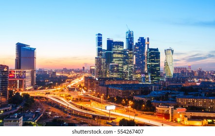high-rise buildings and transport metropolis, traffic and blurry lights of cars on multi-lane highways and road junction at night in Moscow