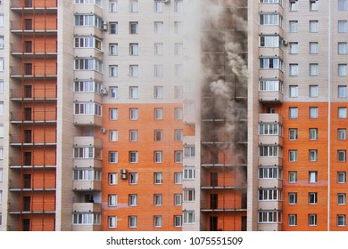 High-rise condominium or apartment burning. Fire in apartments of a large tenement-house. Fire on several floors, the smoke comes out of the windows.