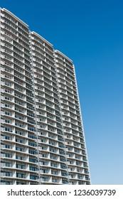 High-rise condominium in Yokohama, Japan. Low angle view of the building against blue sky.