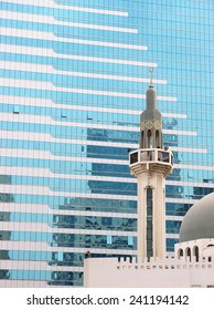 High-rise glass-fronted building juxtaposed with elegant mosque in Abu Dhabi, UAE