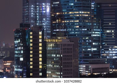 Highrise urban living and apartment windows at night for privacy and residential and commercial zoning concept.  Warm window lights for living and property management.