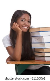 Highschool or college ethnic African-American student sitting by the desk with lot of books in class or library
