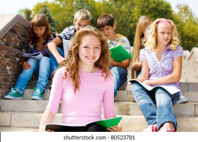 Highschool students with books, sitting on the stairs