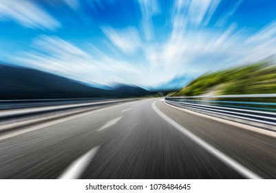 High-speed highway in the mountainous terrain in summer. Motion blur.