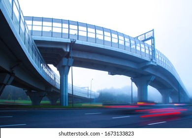 High-speed roads with protective screens. Movement of cars in the fog. High-speed auto movement in different directions. Organization of traffic. Road infrastructure. Road junction.