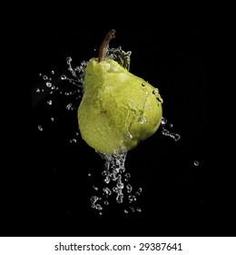 A high-speed shot of a pear with splashing water, isolated on a black background.