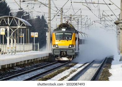 Highspeed train approach to the railway station platform with snow blasting