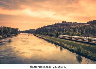 High-speed train on the bank of a river in evening sunset.
