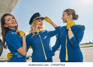 High-spirited young blonde pretty Caucasian stewardess in a pilot cap looking at her female colleague