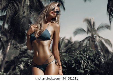 Hight fashion colors,Glamour Portrait of pretty beautiful fashion woman in green bikini posing in summer near the sea and blue sky in sunshine with gorgeous sunglasses,tropic  island girl on vacation