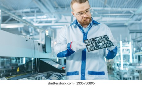 High-Tech Factory: Quality Control Inspector Checks Electronic Printed Circuit Board it for Damages. In the Background Assembly Line for PCB with Surface Mount Pick and Place Technology.