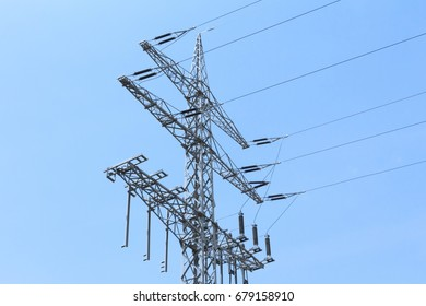 High-tension power line tower carries green electricity energy. Ironman business is transmission of renewable sustainable power to prevent climate change and heal world. Important grid modernization