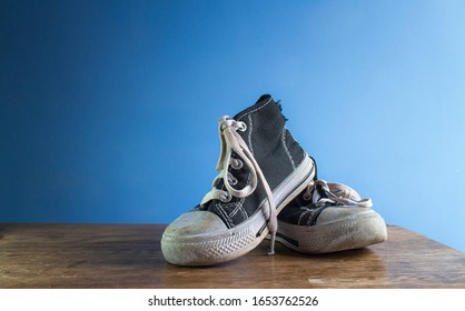High-top shoes belonging to a toddler/child. They're black and white, and are modern and trendy. They have white laces. Shoes are on a wooden table, in front of a plain, blank, blue background.