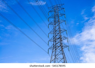 High-voltage cables and voltage pole with blue sky and clouds