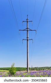High-voltage electric pole with wires on a background of blue sky in a field of blooming lupines