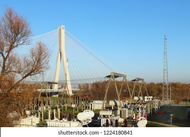 High-voltage electrical network of transformer substation on the background of a modern bridge. Industrial energy. Metal structures in the open air. Insulators and cable. Rzeszow, Poland, Europe.