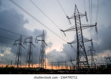 High-voltage electricity grid of power lines, with stormy clouds breaking apart at sunset. Electric transmission towers in a distribution substation in Bucharest, Romania.