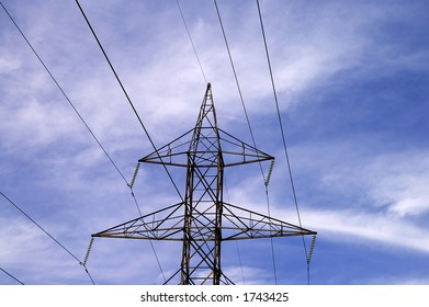 A high-voltage high tension power transmission toweragainst a green plant and blue sky background.