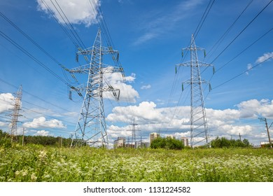 High-voltage power line passes through field to high-rise buildings of urban outskirts