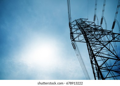 high-voltage power lines at blue sky electricity transmission pylon. Part of high-voltage substation with switches and disconnects.