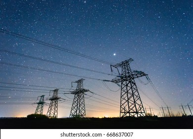 High-voltage power lines on the background of the starry sky. Four electricity pylon of high voltage lines. Silhouette of power lines on the background of beautiful starry sky. Electrical Power Grid.