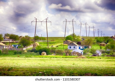 high-voltage power poles against the background of a summer village. electrification of settlements