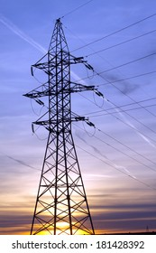High-voltage power supply line metal tower silhouette on beautiful evening sunset vertical view