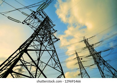 High-voltage power transmission towers in sky background