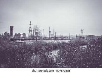 High-voltage tower on the riverbank. First snow. Early winter. The end of autumn. Industrial area. Toned, stylish photo.
