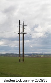 High-voltage transmission lines against the blue sky with gray, gloomy clouds