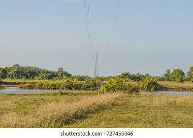 High-voltage transmission tower with blue sky and grassland.