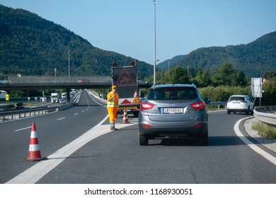 Highway A1, near Vransko, Slovenia - 29 August 2018 - Roadworker diverting cars off highway at roadblock due to accident