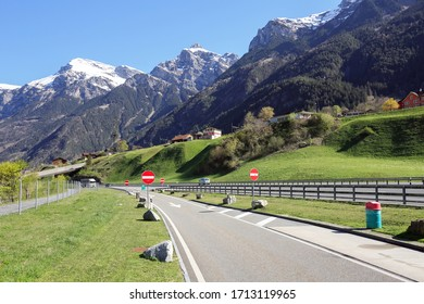 Highway along the river Reuss near the town of Silenen on a sunny spring day. View of the snow-capped Alps. Canton of Uri, Switzerland.