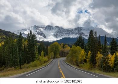 Highway among yellow aspen in San Juan mountains of Colorado