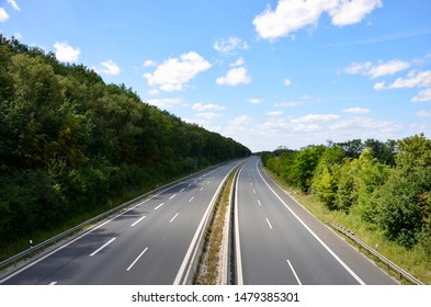 A highway in Bavaria, Germany, few cars on the road, forest on both sides, a sunny day in summer, advertising for traffic, speed, environmental concerns, space for text