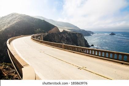 Highway between mountains and pacific ocean. Bixby Bridge at Big Sur