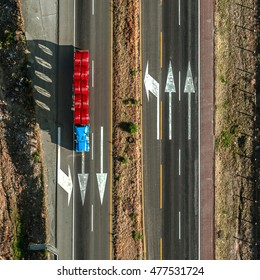 Highway bird's-eye view with truck passing over white arrows in pavement