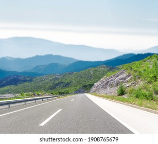 Highway with blue sky and rocky mountains on a background