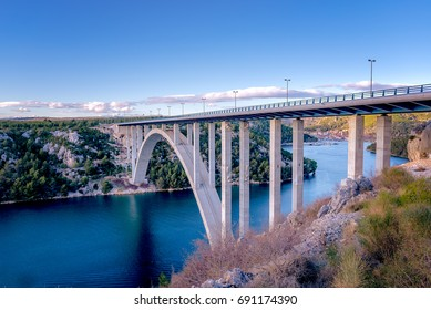 Highway bridge over the Krka river, town of Skradin in background, the bridge is painted in sunset colors