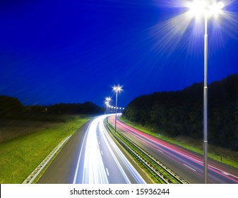 highway by night with long shutter speed with illumination and  dark blue sky