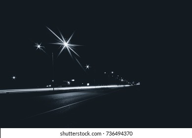 Highway in the city at night with streetlights and long exposure light streaks from cars background