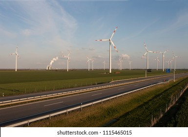 Highway is crossing field of windmills and power Station on pretty day